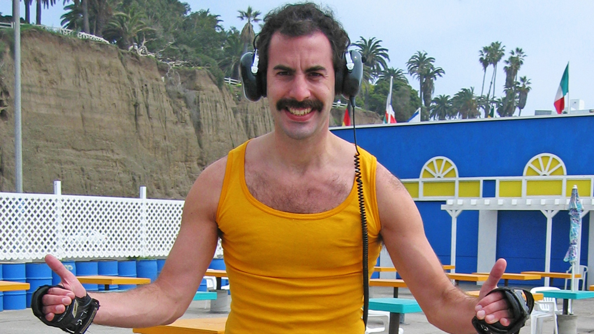 Borat stands in a vest