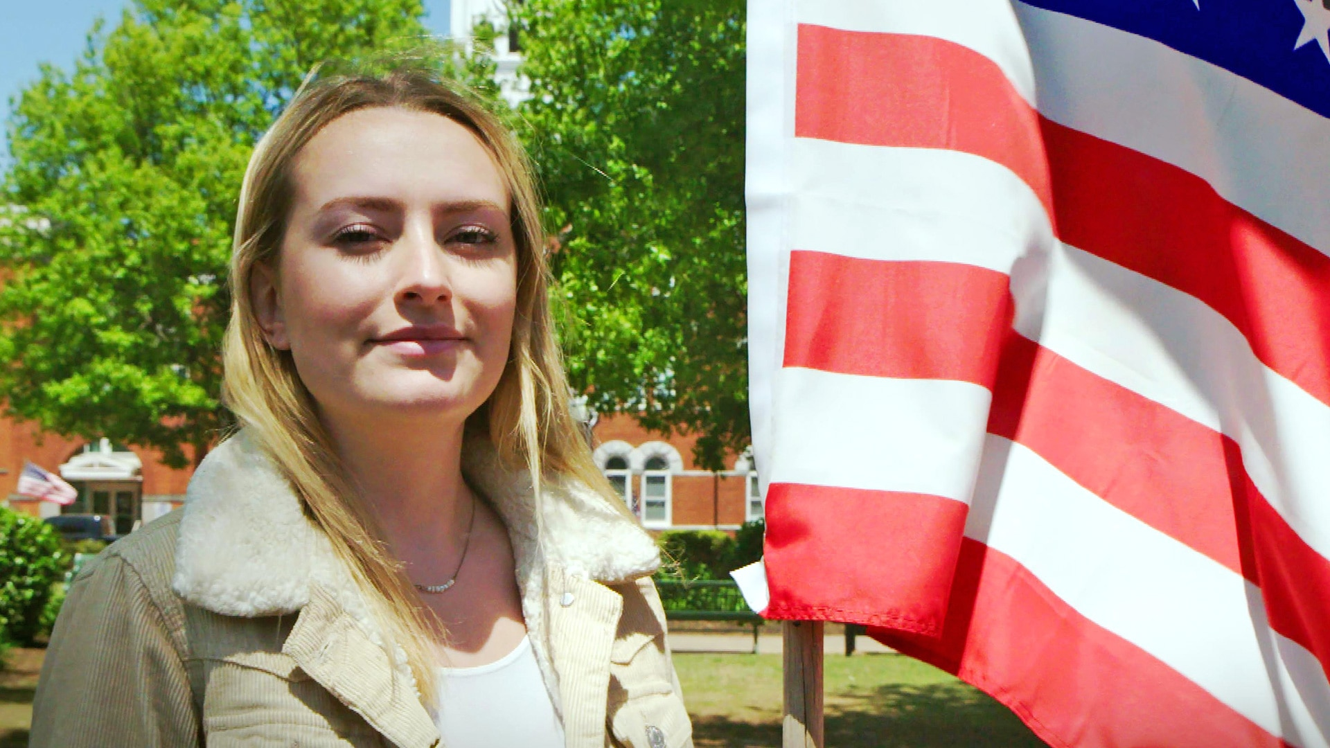 Amelia Dimoldenberg stands next to an American flag