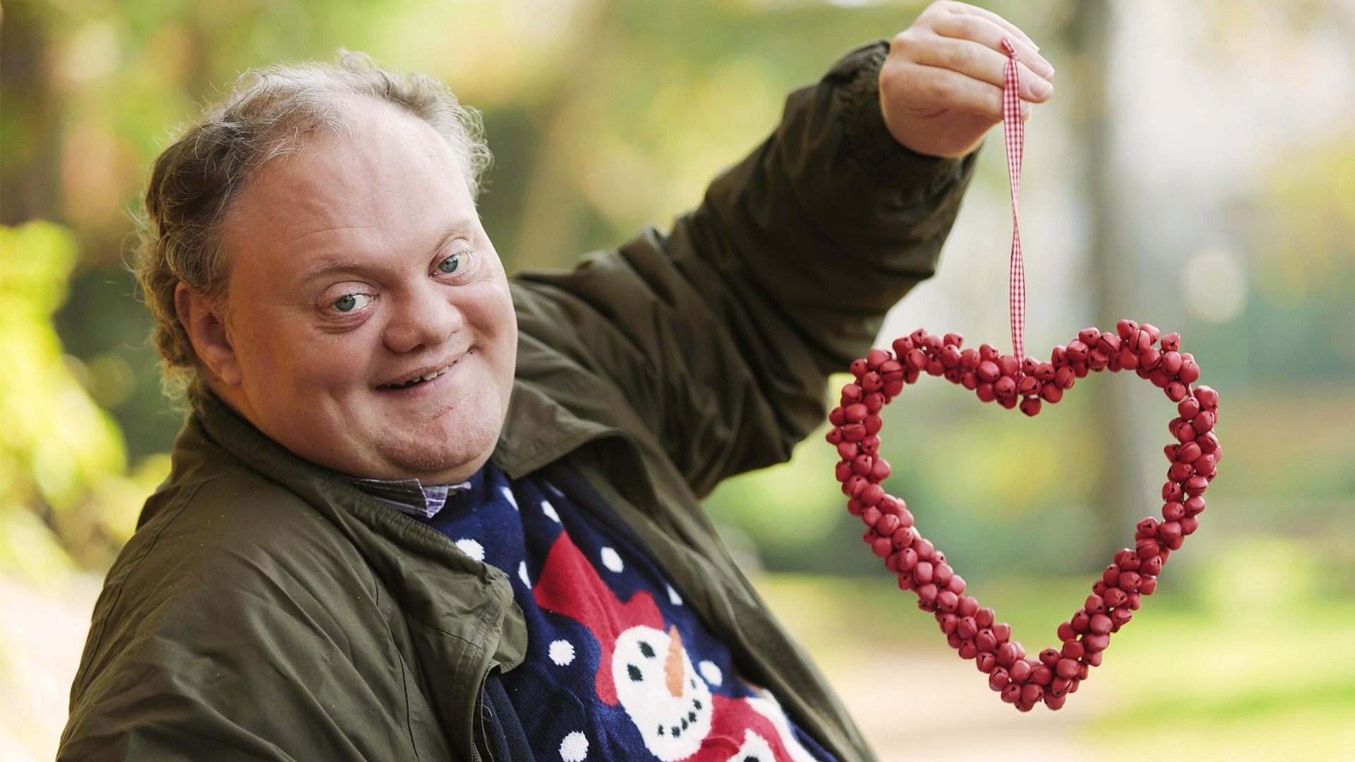 Shaine from The Undateables holds up a love heart shaped wreath