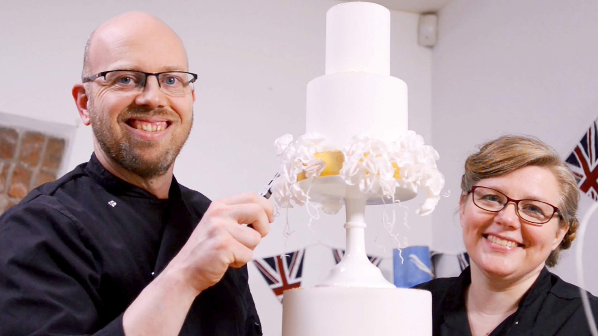 Two cake makers pose with their cake