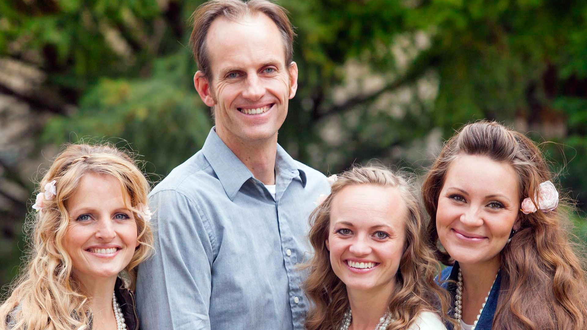 A Mormon man poses with his three wives