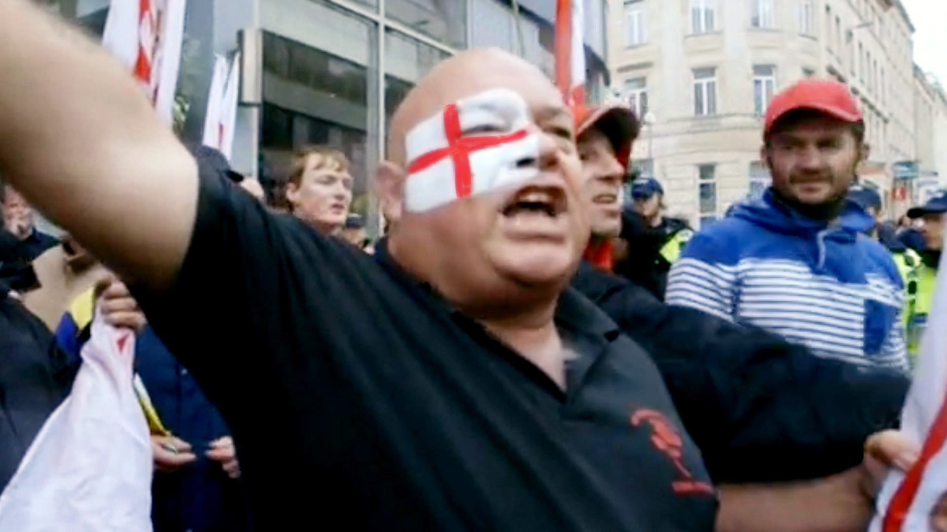 Man with English flag face paint chants