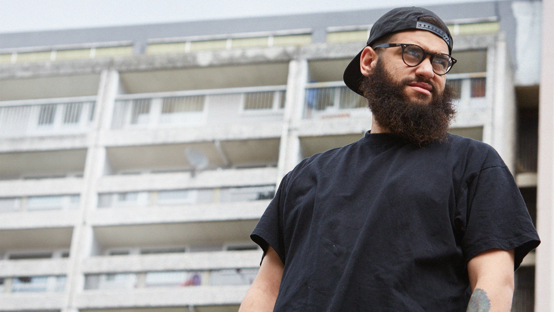 Jamali Maddix standing in front of a block of flats